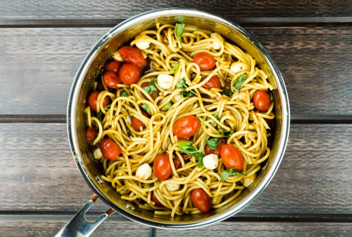 Pasta with tomatoes, cheese, and basil in a pot.